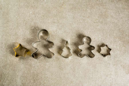 Christmas cookie cutters on gray kitchen stone table - christmas tree, gingerbread man, stars. Top view copy space, christmas baking concept Stock Photo