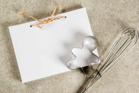 Christmas baking background, notepad for recipes, whisk for whipping, gingerbread man cookie cutter on gray kitchen stone table top view copy space 版權商用圖片