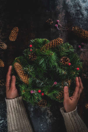 Preparation for xmas holidays. Woman decorating christmas green wreath with pine cones and red winter berries, on dark rusty  background, top view copy space, female hands in picture