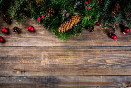 Christmas fir tree branch with pine cones and decorations on wooden table. Top view, copy space.