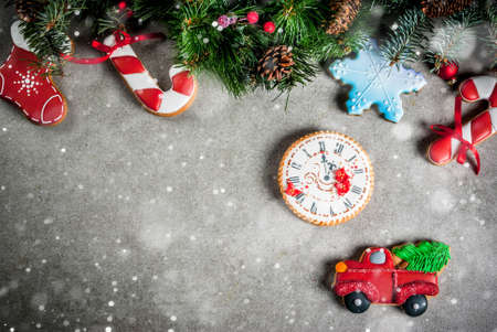 Christmas background with fir tree branch, homemade colorful gingerbread cookies, pine cones and decorations on grey stone table. Top view, copy space