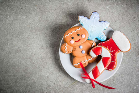 Plate with homemade colorful glazed Christmas cookies on stone gray table, top view copy space