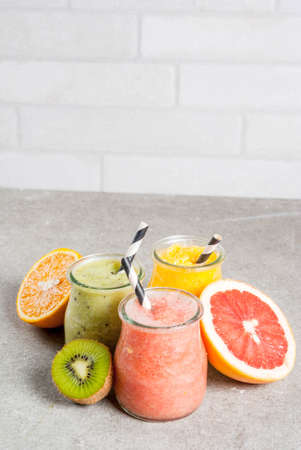 Detox organic diet drinks, homemade tropical smoothies - kiwi, orange, grapefruit, in portioned jars, with ingredients, on a gray stone table. Copy space