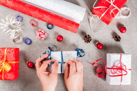 Preparing for Christmas holidays. Gifts and decorations on the table, girl hands in the picture ties up the ribbon on the gift. Top view