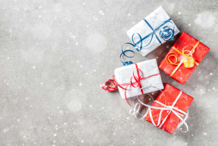 Christmas background with decorated gifts. Gray background, snow effect, Top view copy space