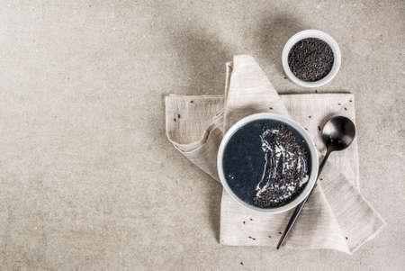 트렌디 한 비건 음식 조리법, 참깨와 코코넛 밀크와 함께 검은 참깨 스프, 회색 돌 테이블, 복사 공간 윗면보기