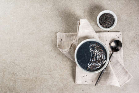 Trendy vegan food recipes, Black Sesame Soup with sesame seeds and coconut milk, grey stone table, copy space top view 스톡 콘텐츠