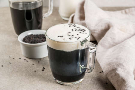 Trendy vegan food recipes, Black Sesame Cappuccino with sesame seeds and whipped coconut milk, grey stone table, copy space