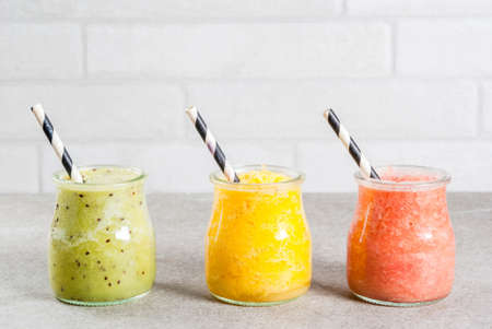 Detox organic diet drinks, homemade tropical smoothies - kiwi, orange, grapefruit, in portioned jars, on a gray stone table. Copy space
