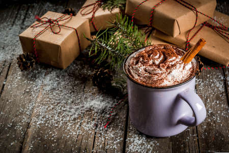Christmas concept, hot chocolate or cocoa with whipped cream and spices, Christmas gifts, candy canes, Christmas tree branch and pine cones, on old rustic wooden table with snow, copy space