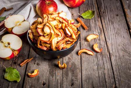 自家製の日干しオーガニックリンゴスライス、サクサクのリンゴチップ、新鮮なリンゴとシナモンと古い素朴な木製のテーブルの上。スペースのコ