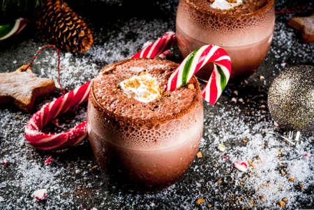 Traditionele kerstdrankjes. Noordpoolcocktail met snoepgoedsnoepjes, pepermunt, warme chocolademelk of cacao, gemberadvertemelk. Donkere achtergrond, met Kerstdecoratie, kopie ruimte