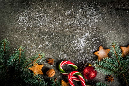Christmas dark background with christmas tree branches, pine cones, candy cane sweets, gifts, christmas balls and decorations, top view copy space Lizenzfreie Bilder