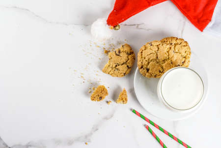 Christmas concept, greeting card. Milk glass and cookies for Santa Claus with Santas hat on white marble background, copy space top view
