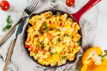 Mexican food recipes, Revoltillo de Huevos, Scrambled Eggs a la Dominicana, in portioned skillet, on white marble table,copy space top view