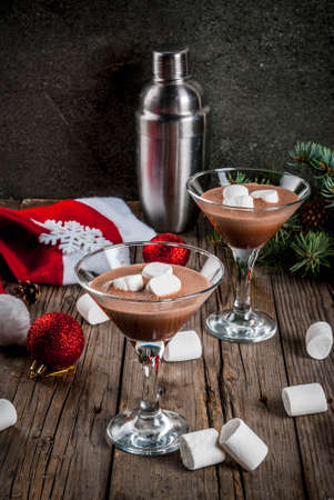 Ideas for Christmas party drinks, homemade Hot Chocolate Martini cocktails with marshmallow, on old rustic wooden table with christmas decorations, copy space Lizenzfreie Bilder