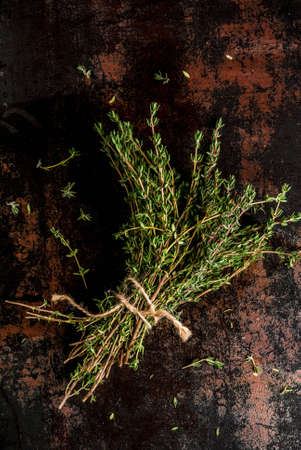 Bunch of fresh organic thyme on an old metallic rusty black background, copy space top view