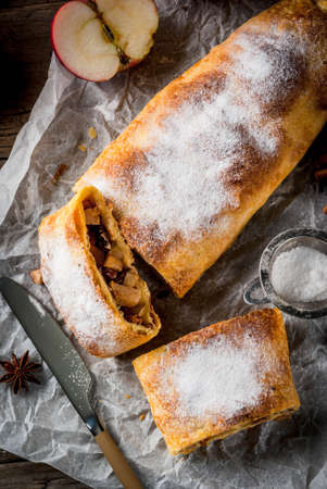 Home autumn, summer baking, puff pastries. Apple strudel with nuts, raisins, cinnamon and powdered sugar. On a wooden old rustic table. Sliced, with ingredients. Copy space top view Lizenzfreie Bilder