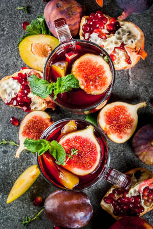 Warming autumn, winter cocktail drinks recipes. Hot red fruit sangria with apples, plums, figs, pomegranate, mint, cinnamon, thyme, lemon. On dark stone table, copy space top view Lizenzfreie Bilder