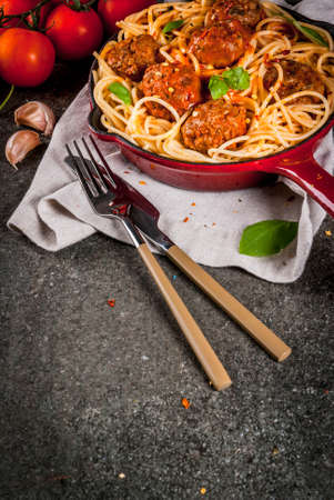 Spaghetti pasta with meatballs, basil tomato sauce in red cast iron pan, on black stone table copy space