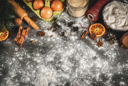 Christmas, New Year holiday cooking background. Ingredients, spices, dried oranges and baking molds, Christmas decorations (balls, fir-tree branch, cones), On black stone table, copy space Lizenzfreie Bilder