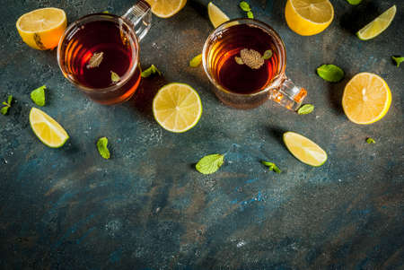 Black tea with lemon and mint on dark blue concrete stone background, copy space top view