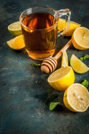 Black tea with lemon and mint on dark blue concrete stone background, copy space