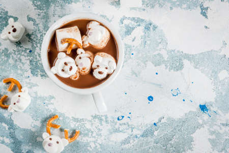 Idea for a childrens Christmas snack, hot chocolate with teddy bears and deer marshmallow. On a light blue background, copy space top view Archivio Fotografico
