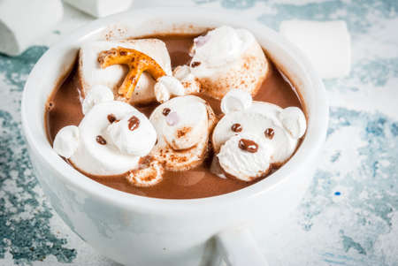 Idea for a childrens Christmas snack, hot chocolate with teddy bears and deer marshmallow. On a light blue background, copy space