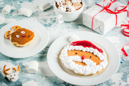 Idea for a childrens Christmas breakfast: pancakes decorated like Santa Claus and deer, cocoa with teddy bears and deer marshmallow. On a light blue concrete background, with xmas gift Archivio Fotografico