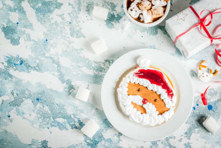 Idea for a childrens Christmas breakfast: pancakes decorated like Santa Claus, cocoa with teddy bears and deer marshmallow. On a light blue background, with xmas gift top view copy space