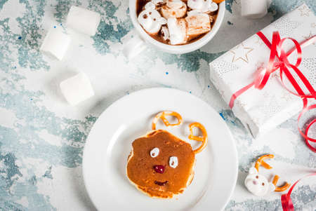 Idea for a childrens Christmas breakfast: pancakes decorated like Santas deer, cocoa with teddy bears and deer marshmallow. On a light blue background, with xmas gift top view copy space