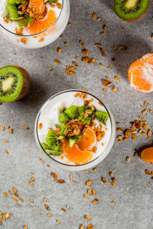 Healthy tangerine and kiwi yogurt granola dessert for breakfast, with ingredients, gray stone table, copy space top view Archivio Fotografico