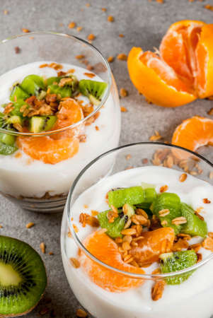 Healthy tangerine and kiwi yogurt granola dessert for breakfast, with ingredients, gray stone table, close view