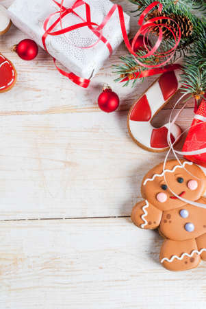 Festive Christmas wooden white background, with Christmas tree branches, pine cones, decorations, Christmas gifts and gingerbread, top view copy space