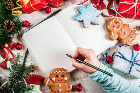 Festive Christmas wooden white background, with Christmas tree branches, pine cones, decorations, Christmas gifts and gingerbread and notepad, girl hand writing in picture above copy space Archivio Fotografico