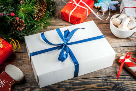 Decorated Christmas gifts boxes on a wooden table, with a cup of hot chocolate, gingerbread and Christmas tree branches. Copy space Archivio Fotografico