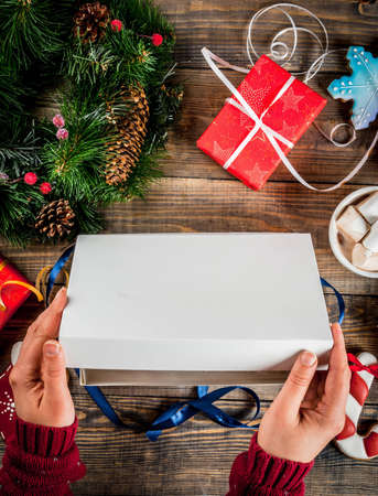 Girl is opening Christmas gift on a wooden table, with christmas presents, cup of hot chocolate, gingerbread and Christmas tree branches. Copy space top view
