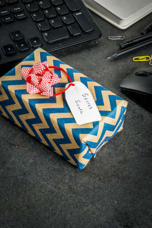 Office Christmas celebration concept, the idea of sharing gifts secret Santa. Keyboard, mouse, notebook, pens, pencils, Christmas gift. Black office table, copy space