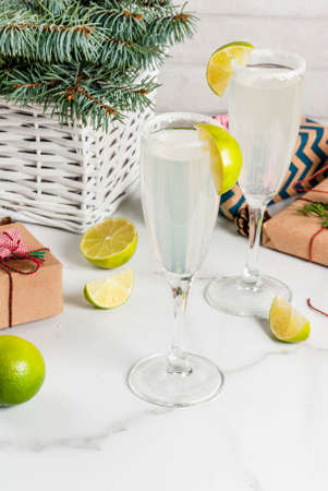Ideas for Christmas and New Year drinks. Champagne Margarita cocktails, garnished with lime and salt. On white table with xmas decorations, copy space
