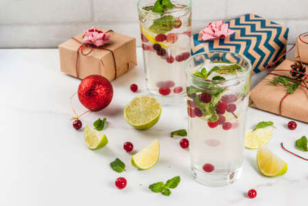 Fall and winter refreshment drink, cranberry mojito cocktail with lime and mint, with christmas gifts and decorations on white table, copy space