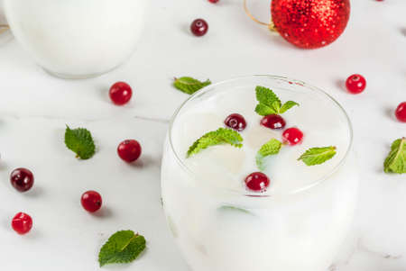 Fall and winter refreshment drink, White Christmas Mojito cocktail with cranberry and mint, on white table, copy space