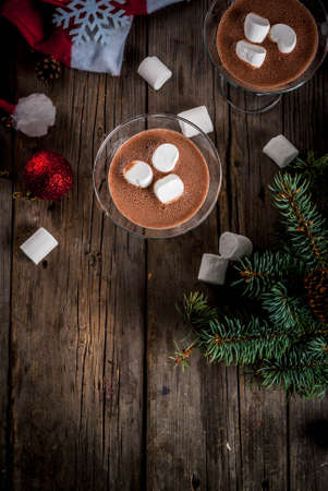 Ideas for Christmas party drinks, homemade Hot Chocolate Martini cocktails with marshmallow, on old rustic wooden table with christmas decorations, copy space top view