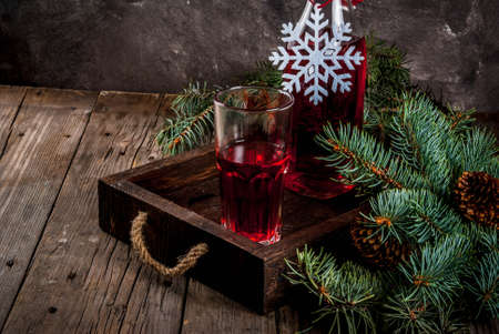 Autumn, winter drinks. Homemade cranberry juice, in a bottle and glasses on an old wooden rustic table, with Christmas tree branches.copy space