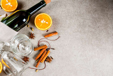 Christmas hot drinks recipes, Set of ingredients for mulled wine: wine bottle, glass cups, spices, orange. Gray stone background, copy space top view Archivio Fotografico