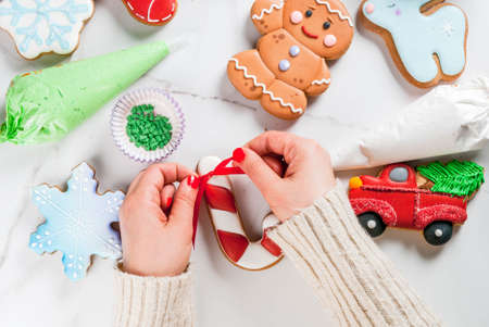 Preparing for Christmas, decorating traditional gingerbread with multicolored sugar icing, white marble table. Girl (hands in picture) knot ribbon bow on candy cane gingerbread, top view copy space Archivio Fotografico