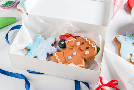 Preparing for Christmas, decorating traditional gingerbread with multicolored sugar glaze, cookies, gingerbread in a white gift box, with ribbon bow, on a white marble table copy space Archivio Fotografico