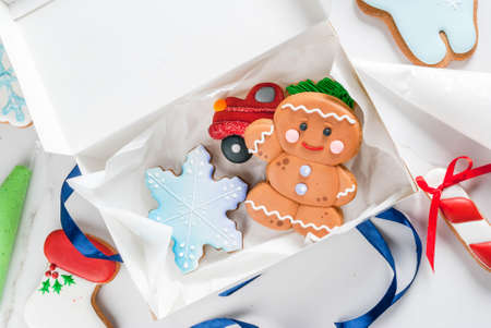 Preparing for Christmas, decorating traditional gingerbread with multicolored sugar glaze, cookies, gingerbread in a white gift box, with ribbon bow, on a white marble table top  view copy space