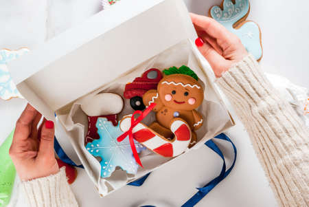 Preparing for Christmas, decorating traditional gingerbread with multicolored sugar glaze, the girl folds the cookies in a white gift box, with ribbon bow, on a white marble table copy space top view