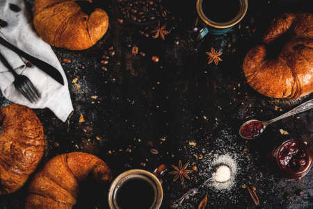 Homemade continental breakfast, coffee with spice, cane sugar, croissants. jam on a black rusty metal table, copy space top view frame